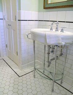 White bathroom with black tile accents + sink.