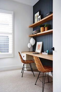 Navy paneled wall behind desks + open wood shelving + long wood desk for 2 + rattan desk chairs