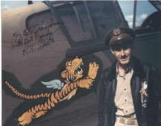 """R.T. Smith next to the Disney """"Flying Tiger"""" decal on the side of P-40 Tomahawk #40 in Kunming, China on May 23, 1942."""