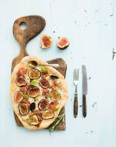 Rustic homemade pizza with figs, prosciutto and mozzarella cheese on dark wooden serving board over  - Rustic homemade pizza with figs, prosciutto and mozzarella cheese on dark wooden serving board over light blue backdrop. Top view