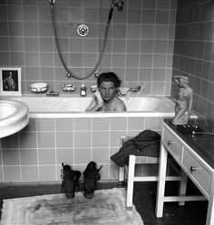 Lee Miller in Hitler's apartment at 16 Prinzregentenplatz. Note the combat boots on the bath mat now stained with the dust of Dachau; and a photograph of the previous owner of the flat propped on the edge of the tub. Published in Scrap Book by Roland Penrose, 1981, page 133, La Poligrafa, Barcelona. - 1017 | LeeMiller