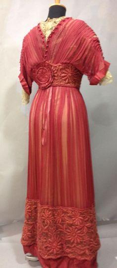 robe habillé, vers 1910. Satin et mousseline plissée framboise rebrodée de fleurs en soie floche. Dos orné d'une rosette en gros grain rose (acc. doublure changée)