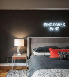 Quarto com muita personalidade, seja na parede preta, no uso da frase em neon e a cabeceira em tecido.
