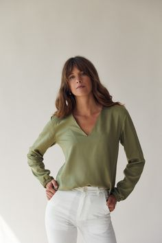 This is a green relaxed fitting blouse with long sleeves, a v-shaped neckline and an elastic band around the wrists. It is made of a very soft, luxurious fabric. We recommend tucking it in! 100% TENCEL™ fibers from Austria, woven in Spain and sustainably dyed using the Iris method. Made in Germany. Green Blouse, V Neck Blouse, Austria, Iris, Organic Cotton, Spain, Germany, Label, Neckline