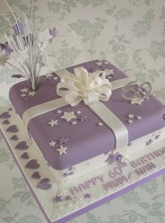Purple and white birthday cake with bow