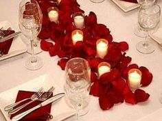 silk rose petals and votives... simple but pretty. I like this idea. I could do purple and black petals mixed.