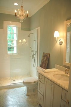 Take a typical ho-hum bathroom layout and open it up with a walk-in tile shower and clear glass. A chandelier and sconce lights add romantic charm to the space.