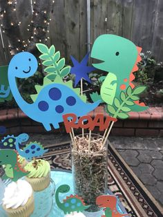 Dinosaur centerpiece comes with two large dinosaurs Two leaf accent pieces Roar accent piece  Also available to match this theme Cupcake toppers Happy birthday banner Goodie bags High chair banner