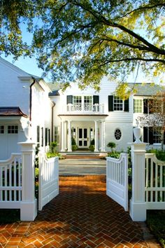 thehandbookauthority:thefoodogatemyhomework:White washed brick and white clapboard asymmetrical traditional by the Lane Group Inc. Black shutters, oval window, urn detailing on the fence posts, Chippendale style fretwork, flared hip style overhang above the garage doors - its the details that make the difference