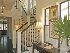 Classic entry. French doors w/ transoms, staircase featuring white risers and dark treads.  Dark hardwood.  Lanterns.  Gallery frames in gold.