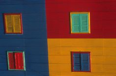 La Boca in Buenos Aires  is full of these brightly painted buildings. The story is that the dock workers who lived in this area were poor and had to build their houses using cast-away  pieces of corrugated metal they found on the docks. And they painted those houses with paint that they found. So they never had enough paint of the same colour to cover the entire house, so the houses became a brightly coloured patchwork. Argentina Travel, Corrugated Metal, Metal Buildings, Horse Riding, Palermo, South America, Waterfall, It Cast, City