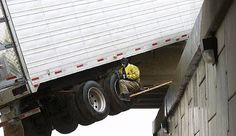 Place: Gallup, New Mexico. An unidentified member of the tow truck company called to remove a truck from the overpass sits dangerously under the truck as he attempts to get a strap under it.