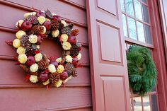 Want to recreate the wreathes of Colonial Williamsburg? First, choose a color palette. Then, choose materials based on what would fit in with that scheme. Sketch out the design before getting started.   Here, pomegranates, strawflowers, and cones from the Virginia pine complement the color scheme of their backdrop, Wetherburn's Tavern.