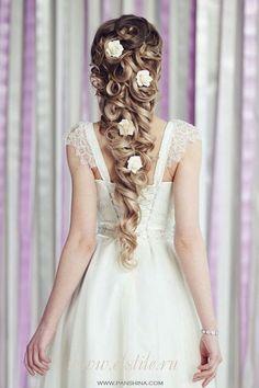 Delicados pins de flores de tecido em um penteado cuidadosamente elaborado.