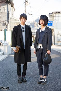 Two student on the street in Harajuku. He's wearing a resale coat over a UNIQLO items with creepers and a Freak's Store clutch. She's wearing a jacket over a matching striped top and cropped pants from Lowrys Farm, brogues, and a WEGO heart-shaped clutch.
