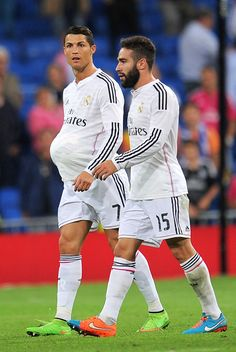 Cristiano Ronaldo leaves the pitch with the ball under his shirt beside Daniel Carvajal after scoring a hat trick in his team's 5-0 victory over Athletic Club during the La Liga match between Real Madrid CF and Athletic Club at Estadio Santiago Bernabeu on October 5, 2014 in Madrid, Spain.