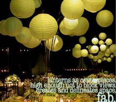 Paper lanterns at the end of bamboo poles or metal rods inserted into a narrow container so they arc out over the table.