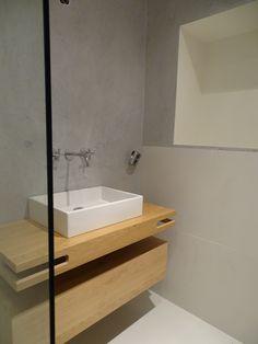 Uitgevoerde betonlook in een lichtgrijze kleur in een badkamer.