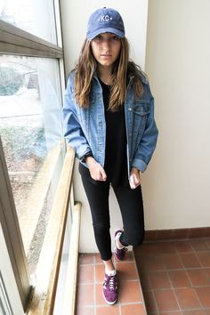 Kansas City native Hannah wears a black tee with black cuffed jeans, an oversized denim menswear jacket, and a blue KC hat. To add a pop of color, she wears magenta Adidas sneakers with her relaxed look.
