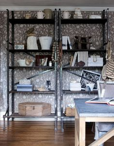 """Library walls are upholstered in a crewel fabric from Brinson's extensive textile collection. """"It's a great background for these old Polish factory shelves,"""" she says. """"It reads as a neutral. And so does that Manuel Canovas micro-check on the chairs."""" Simon Upton  - HouseBeautiful.com"""