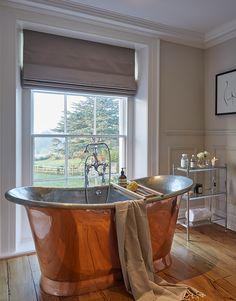 Deep copper soaking tub, roman shade, wide plank wood floors...