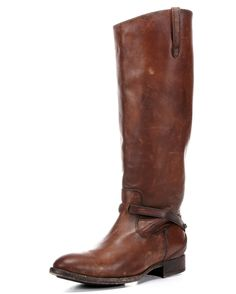 <p>An authentic equestrian. Ultra slim pulls and strap woven through vamp are sleek and stylish. This boot sports an asymmetrical slope at the collar. Volcanic stones distress every square inch, perfectly. A plaque with Frye's name adorns the heel
