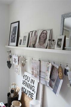 Photos encadrées sur étagère, avec images et journaux accrochés sur un fil