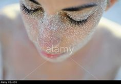 Young attractive woman covered with sand, on the beach © Nano Calvo / Alamy
