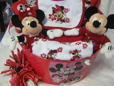 MINNIE MOUSE BABY SHOWER GIFT BASKET THERE IS A ONSEY BURPING CLOTHS AND THREE WASHCLOTHS, A MATCHING DIAPER, WIPE COVER, STUFFED MINNIE AND MICKEY.