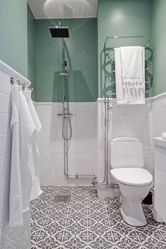 Soothing green walls and a patterned tile floor in a bathroom.