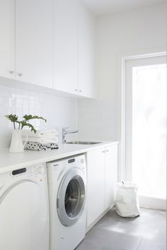 Modern white laundry room features white cabinets paired with white countertops and a white grid tiled backsplash. Modern white laundry room features white cabinets paired with white countertops and a white grid tiled backsplash. Laundry Nook, Laundry Room Layouts, Laundry Room Cabinets, Laundry Room Organization, Laundry In Bathroom, Garage Laundry, Laundry Shelves, Laundry Closet, Garage Cabinets