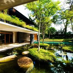 A luxurious and eco-friendly home in Singapore design by Guz Architects. The green and cozy house is designed around a central court where water is the focal point. Lushly planted roof gardens surround it and add to the effect that nature is evident in every part of the house.