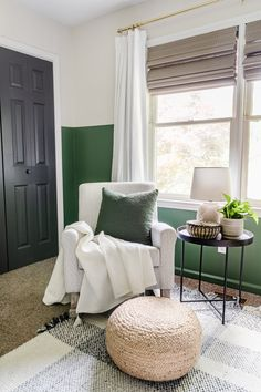 nursery rocker with gray pattern, plaid rug, green paint, blackout curtains, black door, and side table