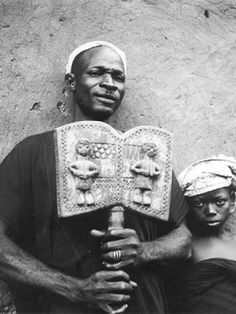 Shango priest and his daughter A priest of Shango in the kingdom of Ketu holding a sacred two-bladed Shango staff (Photo: Ulli Beier)