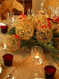 centrotavola natalizio palle natale fatte spago fiocco rosso rami verdi tavola imbandita bicchieri rossi calici cristallo lumini candele bottiglia sedia legno