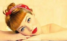 bettie bangs, ginger haired woman with blue eyes and bold black eyeliner, vivid red lipstick and nail polish, red bandanna with white and black details, leaning on hands