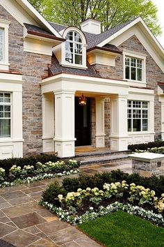 massive white trim on a light brick or stone home. classical style, updated. luxury home