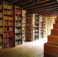 Great use of bookshelves and books to cover walls and serve as room dividers.  #DIY_unfunished_basement #unfinished_basement #basement