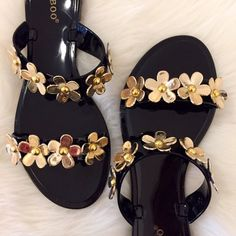 """Gold Floral Studded Vamp Jelly Sandal 7 Size 7! So so so cute. Perfect for summer. That perfect sandal to slip on and off, for beachwear, pool wear, or just casual wear. This flat sandal is jelly construction. Features two straps across the vamp with studded flowers. Perfect for easy on-off wear. Available in whole sizes only! 6-10. If Inbetween sizes. Size up.  15% discount on all 3+ item bundles made with the bundle feature.  Material: PVC (man-made) Sole: PVC Measurement Heel Height: 0.5""""…"""