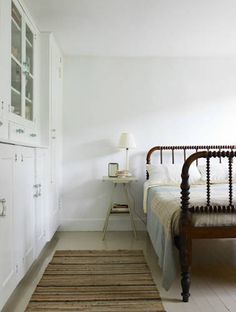 White bedroom with a vintage wooden bed. Via Indoors / Outdoors