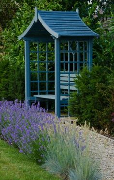 Painted covered seat makes an eye-catching feature.  It is also fun if you pick up on a colour that you've got running like a thread through your garden.  For example, this seat could have been painted in a lavender shade to match the planting.
