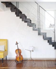 Photo DT75 - ESCA'DROIT®. Escalier d'intérieur design pour une décoration résolument contemporaine ou vintage. Marches Nanoacoustic® lisse pour un escalier métal silencieux. Crémaillère en 'L'. Rampe avec main courante fer plat pour le côté graphique et pour accentuer la transparence des lisses parallèles en câble inox y compris ridoirs et tendeurs. Option main courante non jointive. Finition : acier brut patiné. - © Photo : Nicolas GRANDMAISON