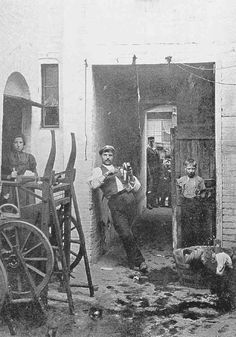 Near Farringdon:  Italians in Caroline Place, off Baker's Row, c. 1900. At the far left is a barrow with metal canisters used for ice-cream...