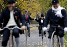 CZECH REPUBLIC: Participants in Prague's annual penny farthing race wearing historical costumes and riding high-wheel bicycles.