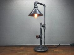 This lamp is a truly unique lighting solution with many applications. A rotating faucet handle serves as a switch to turn the light on and off, a new feature we are excited about! A 60 Watt Squirrel Cage Edison Bulb illuminates an 8 inch rustic steel shade. This lamp is constructed from industrial style black iron piping. The vintage bulb is easy for anyone to change. Power is supplied by a vintage style cloth covered cord. Dimensions: Height - 24in Width - 8in Depth - 12in As each lamp…
