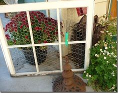 This old window had chicken wire added..now you can hang decorative items on it......like gardening tools I see...