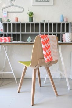 jadore fabric set across neon yellow seated chair with soft pastel grey background shelving decor perfection through color