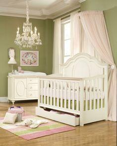 stilvolles Babyzimmer, grüne Wände, weiße Holzmöbel, verspielter Kronleuchter, Babybett mit hellrosa Himmel