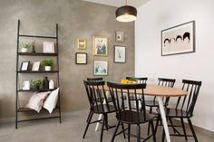Mesa de jantar com tampo de madeira, piso cinza, parede com textura de cimento, cadeiras de madeira na cor preta, luminária pendente preta, prateleira preta e quadros na parede, Apartamento Contemporâneo em Israel  por Dana Shaked