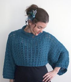 Free Knitting Pattern for Harper Poncho - A cropped cowl-necked lace poncho with buttons to create sleeves. Designed by Katie Rose Pryal. Worsted weight. The original pattern includes a front kangaroo pocket that thepictured projectbyyarnmonster omitted.